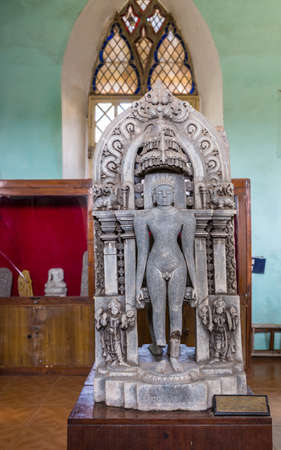 Madikeri, India - October 31, 2013: Ancient Tirthankara, Jain religion, gray stone statue dug out in and displayed at the history museum in decommissioned church of Madikeri Fort. Editorial