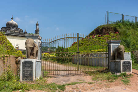 Madikeri, India - October 31, 2013: Entrance gate with elephant statues to the mausoleum domain for the Haleri kings, the Raja Tombs. Blue sky and green vegetation. Dirt road. Blue Sky. Editorial
