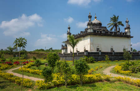 Madikeri, India - October 31, 2013: White and gray Royal mausoleum set in green garden of domain Raja Tombs under blue sky with clouds. Bushes and trees. Editorial