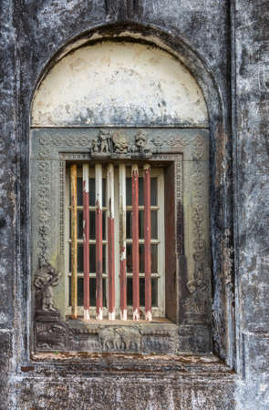 Madikeri, India - October 31, 2013: Closeup of window and rusty decorated metal frame of Royal mausoleum, set in white wall devastated by black mold. Hindu figurines.