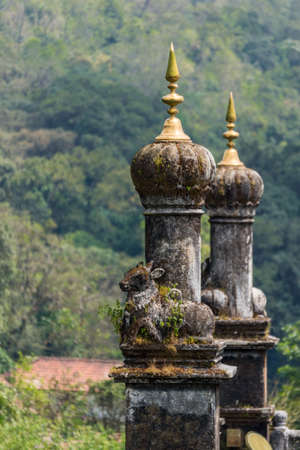 Madikeri, India - October 31, 2013: Turrets on top of Royal mausoleum at Raja tomb. Closeup with base statues of bull. Green hills in back. Shot on roof. Editorial