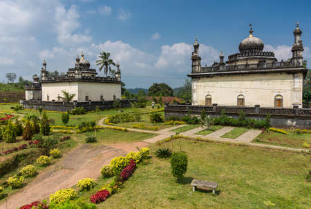 Madikeri, India - October 31, 2013: Three largest white and gray Royal mausoleum set in green garden of domain Raja Tombs under blue sky with clouds. Bushes and trees.