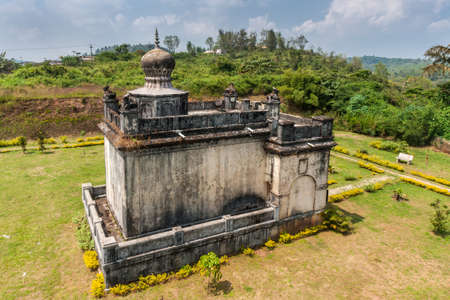 Madikeri, India - October 31, 2013: Closeup on small white and gray Guru Rudrappa mausoleum with bull statue on top, set in green garden of domain Raja Tombs under blue sky. Green vegetation. Shot form roof. Editorial