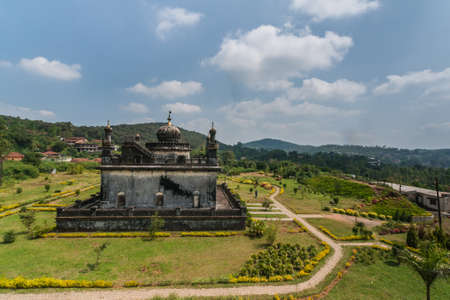 Madikeri, India - October 31, 2013: Small white and gray mausoleum, set in green garden of domain Raja Tombs under blue sky. Green vegetation. Shot form roof.