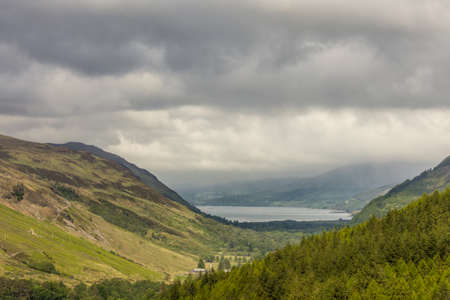 Braemore, Scotland - June 8, 2012: West of Corrieshalloch Gorge along A832 from height look upon Loch Broom under cloudy cloudscape. Green forested mountains. Meadows on slopes and valley. Stock Photo