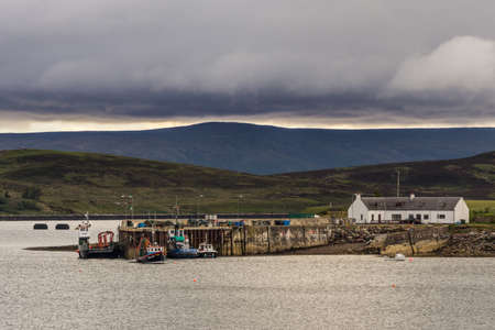 Aultbea, Scotland - June 8, 2012: Calm waters of Loch Ewe with the pier and harbor of Aultbea under dark rainy cloudscape. Dark hills in background.