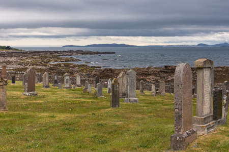 Laide, Scotland - June 8, 2012: Tomgstones at Laide historic beach side cemetery under gray-blue heavy cloudscape. Brown stones and tomb remnants on grass. Gray Atlantic ocean water.