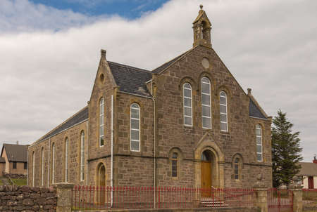 Aultbea, Scotland - June 9, 2012: Christian Congregation Church is brown stone building with small turret, long windows and a fence around. Stock Photo
