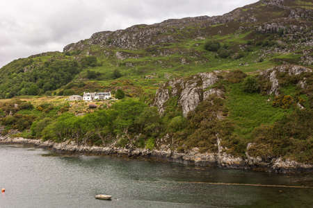 Stromeferry, Scotland - June 10, 2012: White farm mansion on yellowish plateau of green-brown rocky hill at shore of Loch Carron. Gray sky and dark water with sloop. Redactioneel