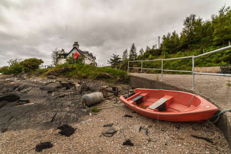 Stromeferry, Scotland - June 10, 2012: Red sloop rests on dry land at shore of Loch Carron among debris. White house and forested hill in back. Under cloudscape. Redactioneel
