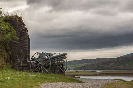 Dornie, Scotland - June 10, 2012: Historic artillery piece outside wall of Eilean Donan Castle. Green vegetation up front and gray cloudscape. Water of Loch and forested mountains as backdrop.