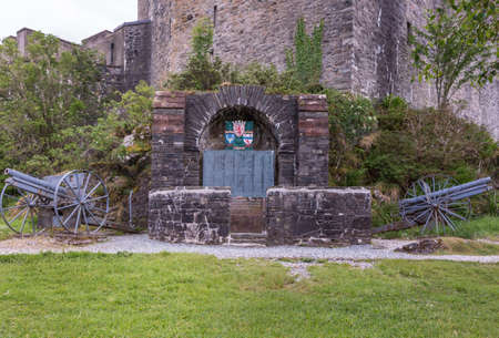 Dornie, Scotland - June 10, 2012: Historic artillery pieces with WW1 war memorial outside wall of Eilean Donan Castle. Emblems and list of in Flanders fallen soldiers. Green vegetation up front.