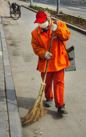Beijing, China - April 26, 2010: Closeup of street sweeper in orange garb and white mouth mask in action with twig broom. Trash collection tricycle in back.