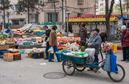 Beijing, China - April 26, 2010: Public market scenery where old woman sells celery and green folded bags off blue tricycle. Other veggies and fruit at stalls in back. Banque d'images - 105370076
