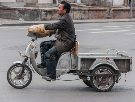Beijing, China - April 26, 2010: Closeup of gray, empty motorized freight tricycle riding on street. Male rider in black leather jacket and brown hand warmers.