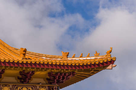 Hacienda Heights, CA, USA - March 23, 2018: Red ochre roof structure of Hsi Lai Buddhist Temple under blue-white cloudscape. Corner tip with figurine decoration. Redactioneel