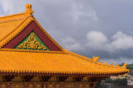 Hacienda Heights, CA, USA - March 23, 2018: Red ochre roof structure of Hsi Lai Buddhist Temple under dark heavy cloudscape. Nook and Corner tip with figurine decoration.