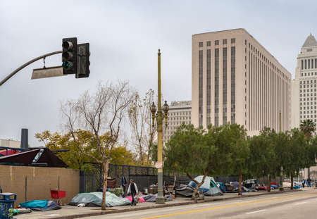 Los Angeles, CA, USA - April 5, 2018: Row of tents and sleeping bags on sidewalk of N. Grand Street downtown. High rise office buildings under silver sky. People, shopping carts and garbage.