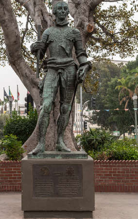Los Angeles, CA, USA - April 5, 2018: Green Bronze statue of Spanish King Carlos III, ordered the founding of El Pueble Los Angeles, shows slender middle-aged man. Back is gray tree trunk, some flags and silver sky.