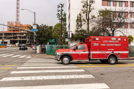 Los Angeles, CA, USA - April 5, 2018: Red Fire Department Rescue Van on street corner of New High and Cesar E. Chavez Avenue. Street view with construction site.