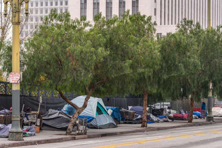 Los Angeles, CA, USA - April 5, 2018: Row of tents and sleeping bags on sidewalk of N. Grand Street downtown. Back is High rise office building. People, shopping carts and garbage.
