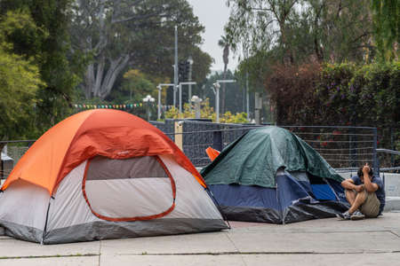 Los Angeles, CA, USA - April 5, 2018: Closeup of small part of Row of tents on sidewalk of N. Grand Street downtown. Back is green of El Pueblo park. Man shows middle finger while hiding face. Editorial