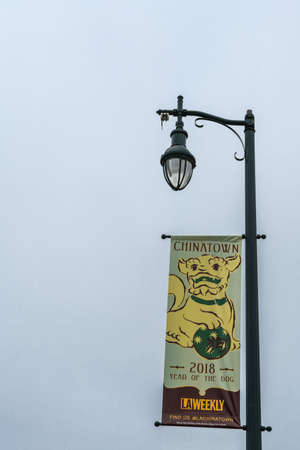 Los Angeles, CA, USA - April 5, 2018: Year of the Dog banner on public lamp posts along the streets of downtown. Chinese style yellow dog drawing on light green background. Sponsored by LA Weekly.
