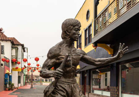 Los Angeles, CA, USA - April 5, 2018: Bruce Lee statue in Central Chinatown. Street scene with red balloon lanterns. Building. Silver sky.