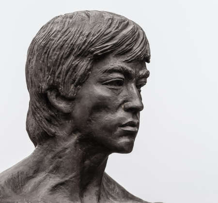 Los Angeles, CA, USA - April 5, 2018: Bruce Lee statue in Central Chinatown. Closeup of his face. Silver sky.