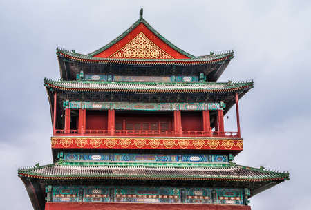 Beijing, China - April 26, 2010: Closeup of colorful upper level of Drum Tower against light blue sky. Plenty of reds, blues, greens and golds.