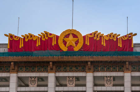 Beijing, China - April 27, 2010: Blood red and deep yellow display of flags, star and wreath on top of National Museum of China on edge of Tienanmen Square. Blue sky.