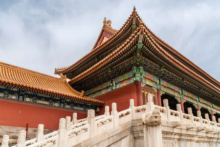 Beijing, China - April 27, 2010: Forbidden City, Elaborate corner structure of hall with orange roof and red walls shows multiple layers and extensive painting of supporting beams, light blue sky.