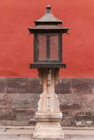 Closeup of antique metal lantern on stone pedestal against red wall. Stock Photo