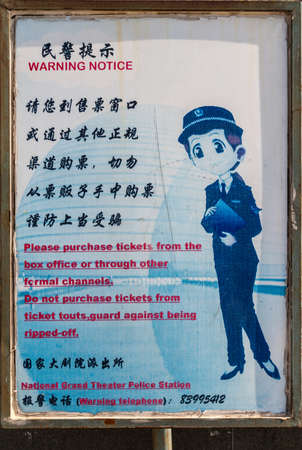 Beijing, China - April 27, 2010: Closeup of freamed sign warning against ticket scalping, resale of entrance documents near Opera. Shows female police officer and text in Mandarin and English. Editorial