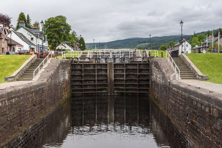 Fort Augustus, Scotland - June 11, 2012: Lock with closed dark brown doors on Oich River Canal showing green grass and white houses on both sides under heavy gray sky. Hills on horizon.