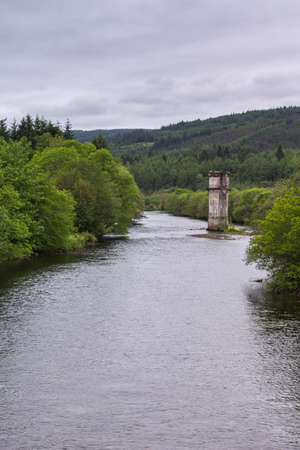 Fort Augustus, Scotland - June 11, 2012: Brown remnant of tower of disappeared bridge over silver Oich River, flanked by green forests along its shores under heavy gray sky. Editorial