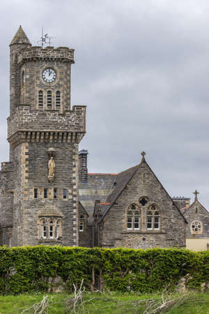 Fort Augustus, Scotland - June 11, 2012: Closeup of the Abbey Highland Club clock tower fronted by garden  under heavy cloudscape.