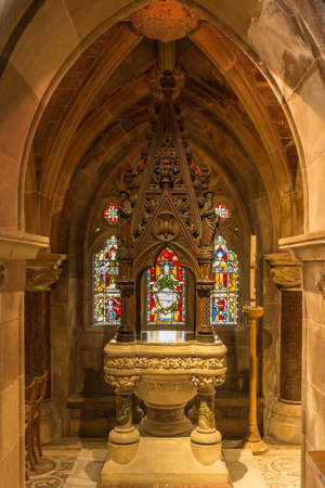 Fort William, Scotland - June 11, 2012: Inside Saint Andrews Church shows baptismal font in large niche with stained window. Portrait format.