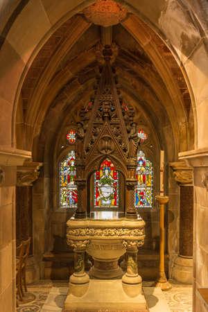 Fort William, Scozia - 11 giugno 2012: All'interno della chiesa di Sant'Andrea mostra il fonte battesimale in una grande nicchia con finestra macchiata. Formato verticale.