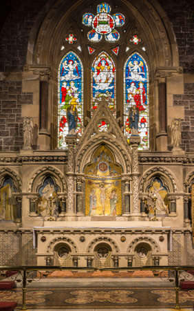 Fort William, Scotland - June 11, 2012: Inside Saint Andrews Church shows the modern altar in front of stone artwork backdrop. Stained glass window in back. Portrait format.