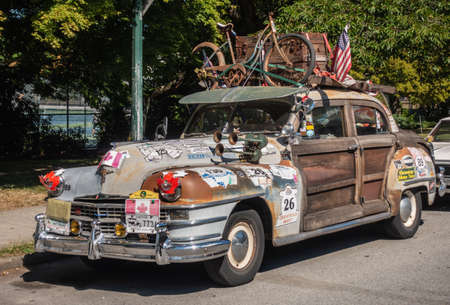 Vancouver, Canada - July 15, 2018: Closeup of vintage Chrysler car with wooden doors, heavily decorated with stickers, a bike and chest on top, and the USA and Canadian flags.