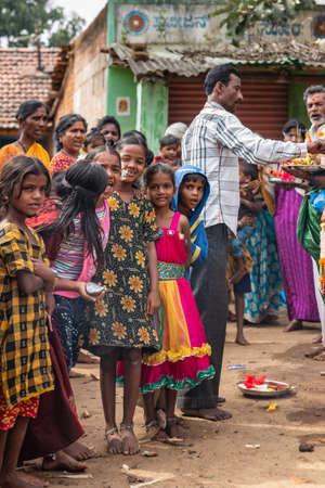 Belathur, Karnataka, India - November 1, 2013: Group of smiling young girls bidding farewell to departing pilgirms during ceremony.