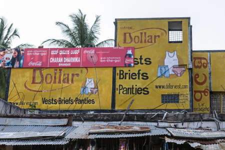 Shravanabelagola, Karnataka, India - November 1, 2013: Yellow billboard above gray corrugated meta; roof showing Coca-Cola and underwear products.