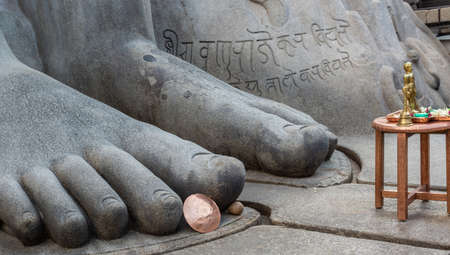 Shravanabelagola, Karnataka, India - November 1, 2013: closeup of giant blue gray granite feet of Bhagwan Bahubali. Props such as brown table and copper shield show the giant size of the statue.