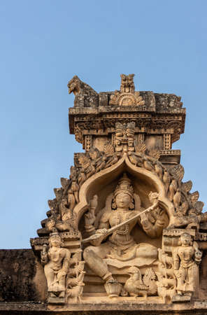 Shravanabelagola, Karnataka, India - November 1, 2013: Brown stone with black mold deity statue in niches on edge of roof at Jain Tirth building. Saraswati goddess with instrument.