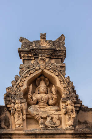 Shravanabelagola, Karnataka, India - November 1, 2013: Brown stone with black mold deity statue in niches on edge of roof at Jain Tirth building. Vishnu with two female deities. Editorial