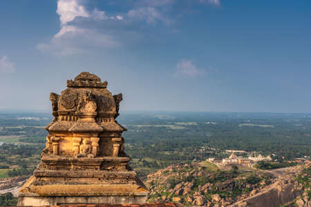 Shravanabelagola, Karnataka, India - November 1, 2013: View onto plains from up at the Jain Tirth with brown stone tower up front and another temple in the far distance. Blue sky.