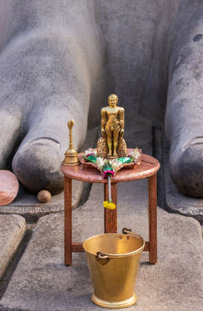 Shravanabelagola, Karnataka, India - November 1, 2013: At the Jain Tirth, between the toes of giant Bhagwan Bahubali statue, stands brown table with golden statue of naked Jain figure, and golden bucket.