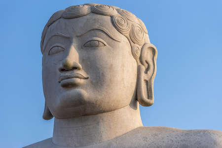 Shravanabelagola, Karnataka, India - November 1, 2013: At the Jain Tirth, closeup of gray granite Giant Bhagwan Bahubali head statue. Blue sky.
