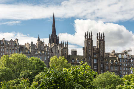 Edinburgh, Scotland, UK - June 13, 2012: New College of University of Edinburgh on market street seen from Scott Monument across green park under blue sky with white clouds.
